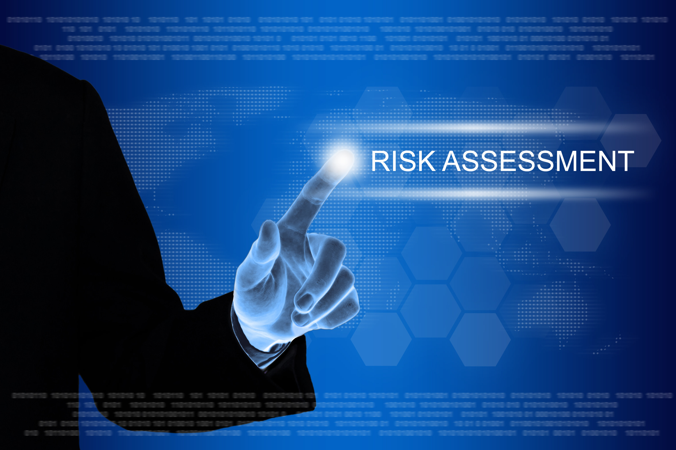 business hand pushing risk assessment button on a touch screen interface